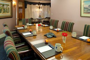 Meetings and Groups, Mezzanine boardroom with a conference table with plush padded chairs around a table.